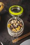 Стекло полное белых йогурта и muesli на темной деревянной доске стоковое фото