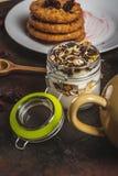Стекло полное белых йогурта и muesli на темной деревянной доске стоковая фотография
