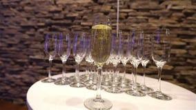 Стекло шампанского на предпосылке пустых стекел, на таблице шведского стола, пена в стекле, движение Шампани камеры видеоматериал