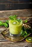 Стекло smoothie кивиа со свежими фруктами на деревянном столе стоковое изображение