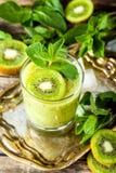 Стекло smoothie кивиа со свежими фруктами на деревянном столе стоковая фотография