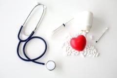 Стетоскоп и красное сердце на белой деревянной предпосылке Медицина и здоровая стоковая фотография