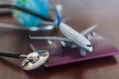 Стетоскоп, документ паспорта, самолет и глобус Глобальная концепция страхования здравоохранения и перемещения стоковые изображения