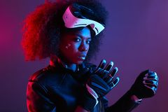 Стильная курчавая темная с волосами девушка одетая в черных кожаной представлениях куртки и перчаток со стеклами виртуальной реал стоковое фото