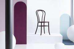 Стильный коричневый деревянный стул на белой платформе в интерьере выставочного зала с большими воздушными шарами и красочными ст стоковое изображение rf
