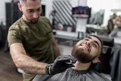 Стильный человек с бородой сидит на парикмахерскае Парикмахер уравновешивает бороду людей с ножницами стоковые фотографии rf