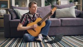 Студент учит сыграть гитару наблюдая онлайн урок в интернете используя ноутбук сидя на поле в живя комнате сток-видео