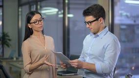 Строгий босс дамы несчастный с работой молодого стажера, проверяя его отчет, терпеть неудачу сток-видео