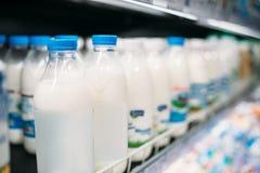 Строка бутылок молока в холодильнике, продовольственном магазине, никто стоковые изображения