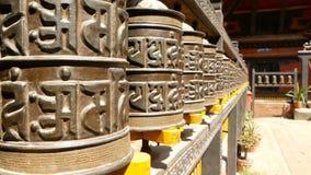 Строка достигших возраста религиозных колес или барабанчиков молитве с жужжанием Om Mani Padme мантры во дворе  виска, квадрата D сток-видео