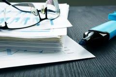 Стог бумаг с финансовым отчетом и стеклами Внутренняя проверка и оценка стоковые изображения rf