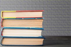 Стог книг с серой кирпичной кладкой на заднем плане, концепция образования, науки стоковые фотографии rf