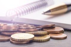 Стог монеток евро евро на старом черном деревянном столе Ручка, тетрадь стоковое фото rf