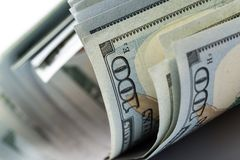 Стог 100 долларов изолированных на белизне стоковое изображение