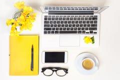Стол домашнего офиса женщин Место для работы с ноутбуком, компьютером, желтой тетрадью, стеклами моды, чашкой кофе, мобильным тел стоковые изображения