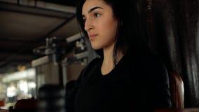 Сторона конца-вверх кавказской девушки брюнета трясет ее подбрюшные мышцы с ее руками на турнике акции видеоматериалы