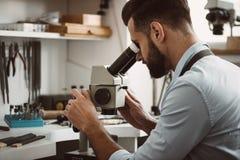 Сфокусированный на процессе Мужской ювелир смотря кольцо через микроскоп в мастерской стоковое изображение