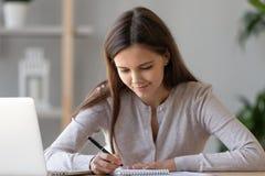 Сфокусированное извещение о сочинительства женщины, используя ноутбук, подготавливая сдать экзамен стоковое изображение rf
