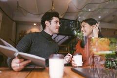 Счастливая азиатские девушка и друзья беседуя говорить на кафе кофейни в университете для того чтобы держать визуальный контакт и стоковые фотографии rf