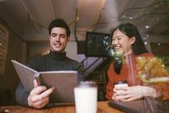 Счастливая азиатские девушка и друзья беседуя говорить на кафе кофейни в университете говоря и смеясь совместно стоковое фото