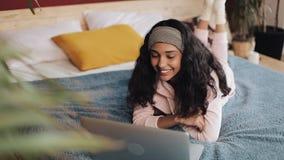 Счастливая Афро-американская девушка лежит на ее животе на кровати окном счастливо беседуя с ее друзьями на видео- звонке видеоматериал