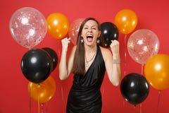 Счастливая женщина в черном платье празднуя кричащие, обхватывая кулаки как победитель на ярких красных воздушных шарах предпосыл стоковое изображение rf