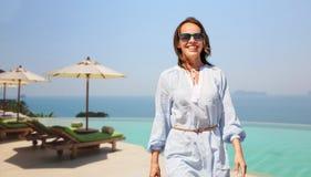 Счастливая женщина идя над бассейном края безграничности стоковое фото rf