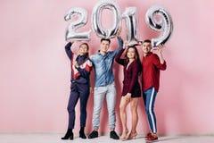 Счастливая компания 2 девушек и 2 парня одетого в стильных одеждах держат воздушные шары в форме 2019 стоковое фото rf