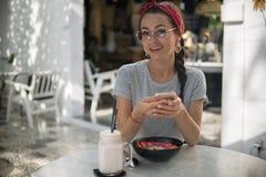 Счастливая молодая женщина используя ее хитрость телефона имея завтрак в кафе стоковое изображение