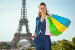 Счастливая молодая женщина с хозяйственными сумками смотря в расстояние стоковая фотография rf