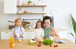 Счастливая молодая мать брюнета с милыми маленькими ребятами имея завтрак стоковая фотография rf