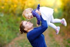 Счастливая молодая мать имея дочь малыша потехи милую, портрет семьи совместно Женщина с красивым ребенком в природе стоковые изображения rf