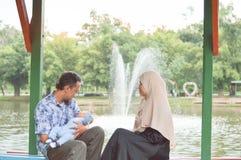 Счастливая молодая мусульманская семья с младенцем наслаждаясь днем на на открытом воздухе парке около фонтана во время времени д стоковая фотография rf
