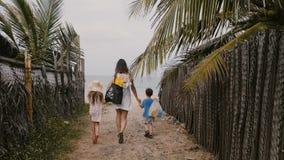 Счастливая молодая семья, мать с меньшим сыном и дочь, идя совместно к красивому пляжу океана на каникулах видеоматериал