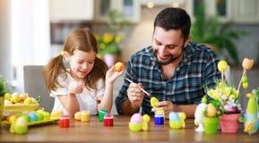 Счастливая пасха! отец и ребенок семьи с зайцами ушей получая готова на праздник стоковое изображение