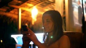 Счастливая привлекательная молодая коммерсантка усмехаясь используя приложение смартфона ходя по магазинам в кафе Лаунж-бара атмо акции видеоматериалы