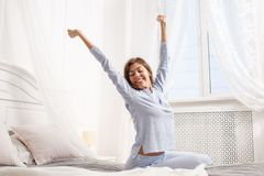 Счастливая девушка брюнета в свет-голубой пижаме протягивает ее оружия вверх по сидеть на кровати сени рядом с окном в стоковое фото rf