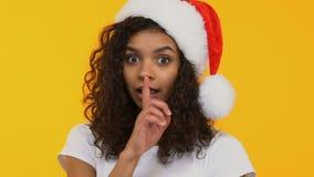 Счастливая девушка в шляпе Санта показывая hush, похваляться настоящего момента Xmas, продажа зимы сток-видео