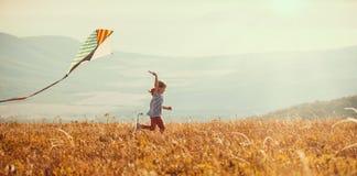Счастливая девушка ребенка бежать с змеем на заходе солнца outdoors стоковое изображение rf