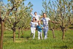 Счастливая семья бежать в парке в лете стоковые фото