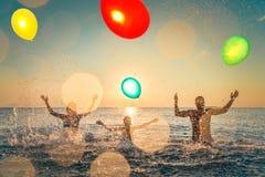 Счастливая семья играя в море стоковое изображение