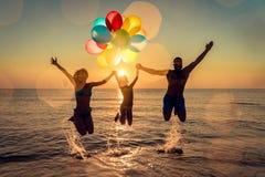 Счастливая семья скача в море стоковая фотография