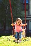 Счастливая смеясь над девушка ребенка на качании мечта детства предназначенная для подростков свобода Спортивная площадка в парке стоковое фото rf