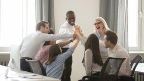 Счастливая разнообразная команда дела работников принималась за teambuilding давать высоко--5 стоковое фото rf