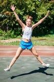 Счастливая sporty женщина скачет в высоту на стадионе спорт, радуется победа стоковое изображение