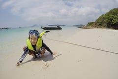 Счастливые азиатские спасательный жилет, маска и шноркель носки девушки, наслаждаются сыграть песок на пляже, достопримечательнос стоковое фото rf