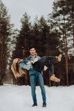 Счастливые жизнерадостные усмехаясь пары молодых людей в костюмах джинсовой ткани в снежном лесе в зиме установьте текст Зимний о стоковое фото rf