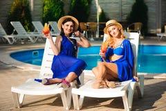 Счастливые лучшие други девушек на изумляя празднике, выпивают коктейли около бассейна и потехи иметь стоковое изображение