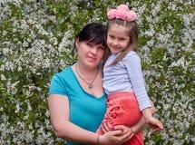 Счастливые мать и дочь в цветках стоковое изображение