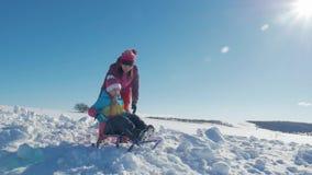 Счастливые мать семьи и дочь ребенка на прогулке зимы outdoors sledging Красивая семья наслаждаться матери и детей видеоматериал